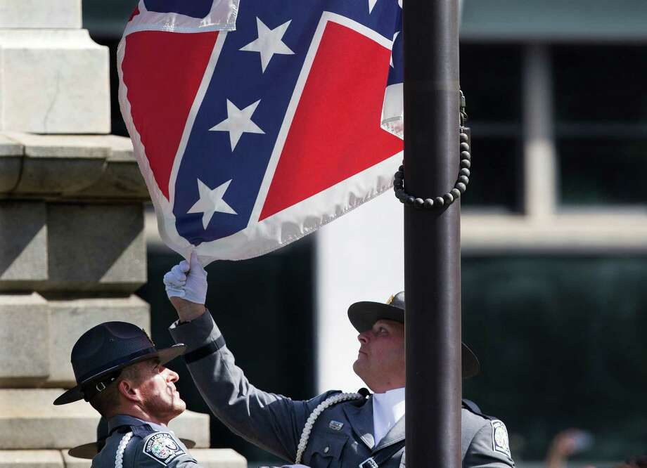 An honor guard from the South Carolina Highway patrol lowers the Confederate battle flag as it is removed from the Capitol grounds Friday, July 10, 2015, in Columbia, S.C. The Confederate flag was lowered from the grounds of the South Carolina Statehouse to the cheers of thousands on Friday, ending its 54-year presence there and marking a stunning political reversal in a state where many thought the rebel banner would fly indefinitely.  (AP Photo/John Bazemore) ORG XMIT: SCJJB201 Photo: John Bazemore / AP