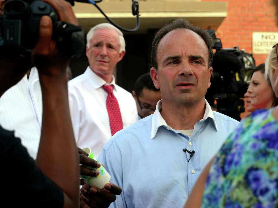 Former Bridgeport Mayor Joe Ganim, right, and current Mayor Bill Finch, in background at left, attend a vigil outside the Trumbull Gardens Community Center on Trumbull Avenue in Bridgeport, Conn., on Thursday June 11, 2015. A shooting at 1 a.m. in a parking lot across the street from the center, left one man dead and seven others injured. Photo: Christian Abraham / Christian Abraham/Hearst Connect / Connecticut Post