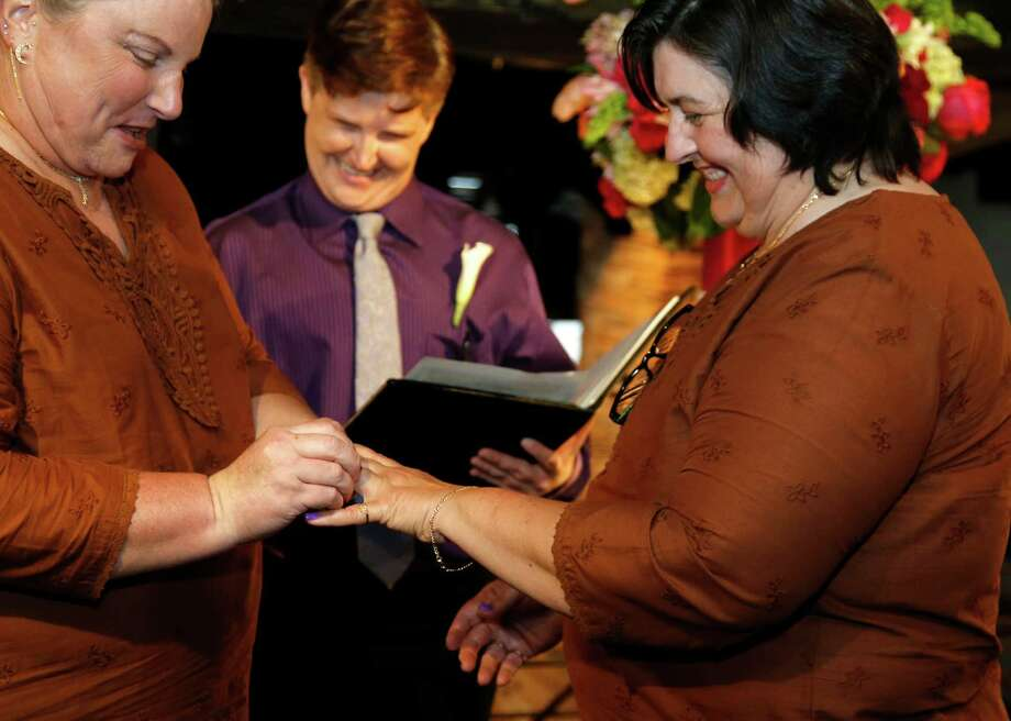 Officiant Erin Bussear, center, performs the wedding service for Sara Rook, left, and Rena Pitre, one of 12 couples who took part in Pop Vows' free wedding event for same-sex couples Friday at Sambuca restaurant in downtown Houston. Photo: James Nielsen, Staff / © 2015  Houston Chronicle