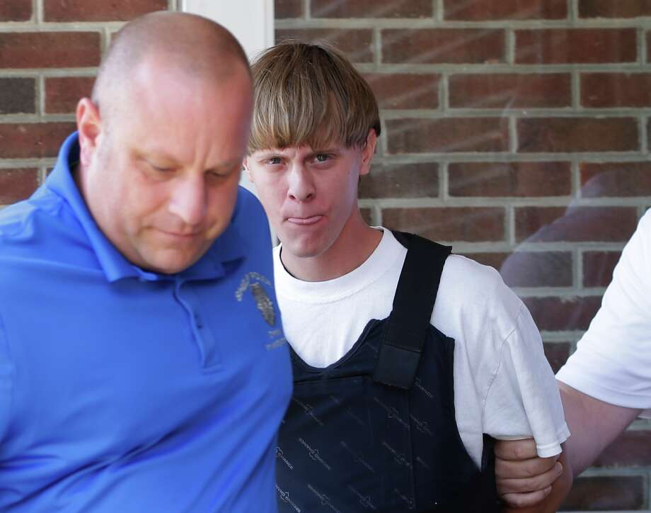 Dylann Roof's drug-related arrest weeks before the Charleston, S.C., shootings should have blocked his purchase of a handgun, law officials say.  on drug charges , center, is escorted from the Sheby Police Department in Shelby, N.C. FBI director James Comey says Roof, the gunman in the Charleston church massacre should not have been allowed to purchase the gun used in the attack, and on July 10 attributed the problem to incomplete and inaccurate paperwork related to an arrest of Roof weeks before the shooting. (AP Photo/Chuck Burton, File) Photo: Chuck Burton, STF / AP