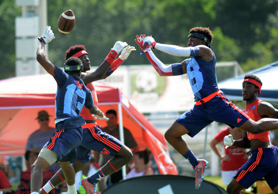 Manvel senior defenders Uryan Hudson, left, and Brandon Bell, right, team up to make a play against a Mesquite Horn receiver during their pool-play matchup in the Adidas 7-on-7 State Championships on Friday in College Station. Photo: Jerry Baker, Freelance