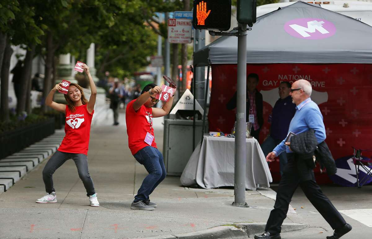 Volunteers Victoria Pareno (l to r), 15 and Vanny Pareno dance outside of the Project More Foundation booth to draw attention to the blood drive on Friday, July 10, 2015 in San Francisco, Calif. The third annual National Gay Blood Drive was on July 10, 2015.