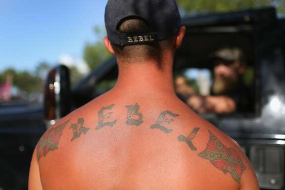 "LOXAHATCHEE, FL - JULY 11:  ""Rebel""  displays a Confederate flag tattoo as he participates in a rally to show support for the American and Confederate flags on July 11, 2015 in Loxahatchee, Florida. Organizers of the rally said that after the Confederate flag was removed from South Carolinas State House it reinforced their need to show support for the Confederate flag which some feel is under attack.  (Photo by Joe Raedle/Getty Images)"