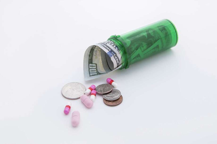 A concept image of money and pills coming out of a bottle that show the high cost of prescription medicine. Photo: Gregory Johnston / Gregory Johnston