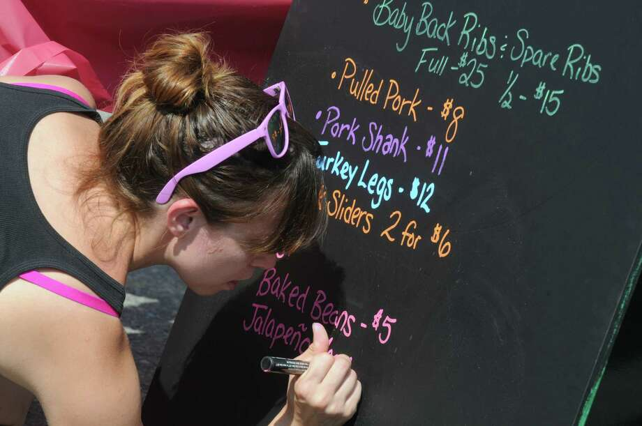 Heidi Jaeger of Bott Leggers fills out their menu board during the Troy Pig Out on Saturday July 11, 2015 in Troy, N.Y. (Michael P. Farrell/Times Union) Photo: Michael P. Farrell / 00032537A