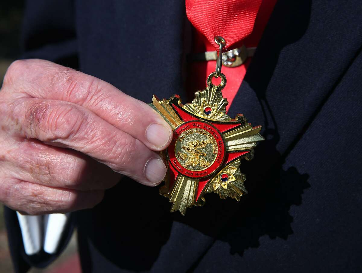 War veteran Don Reid clutches a medal of valor presented to him by the South Korean government, at a groundbreaking ceremony for a Korean War Memorial at the Presidio National Cemetery in San Francisco, Calif. on Saturday, July 11, 2015.