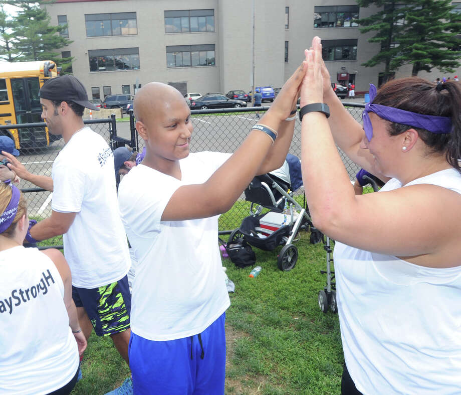 "Harold Alvarez, at center, high-fives Jenna Cappellieri of Team Kids-In-Crisis during the charity kickball tournament to raise money for Alvarez, a Dolan Middle School student, who is battling bone cancer, at Domus Field. Wilner Joseph. who organized the tournament said, ""we are just trying to raise some money to help the family cover the costs for some of the treatment."" Photo: Bob Luckey Jr. / Hearst Connecticut Media / Greenwich Time"