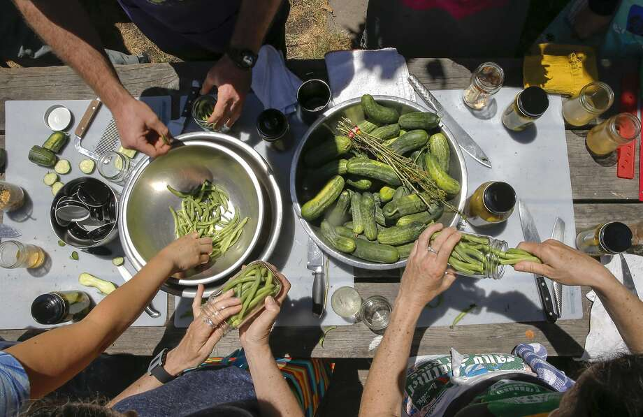 Participants at the recent Happy Girl Kitchen pickling workshop pack jars with green beans and cucumbers to prep for the pickling. Photo: Michael Macor, The Chronicle