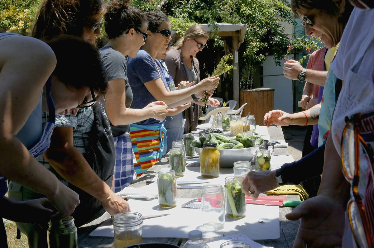 Students combine the ingredients as Todd Champagne during the Happy Girl Kitchen Co. pickling workshop, in Oakland, Calif., on Sat. July 11, 2015.