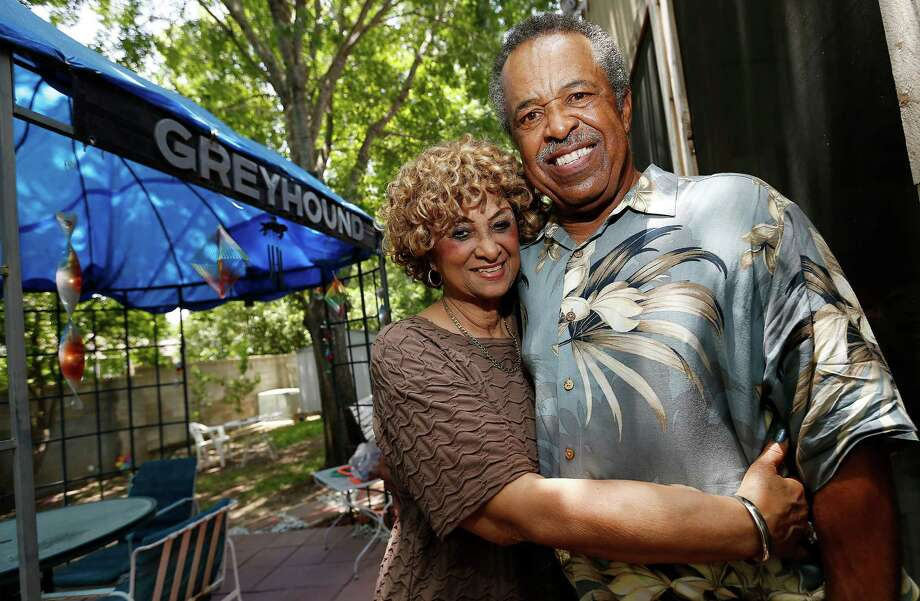 San Antonio native Errol Warren poses with his wife, Phyllis, along with a Greyhound bus logo that he placed on their covered patio. Warren was one of the first African-American long distance bus drivers to be hired in South Texas. Warren retired from full-time driving but still works part-time driving a bus and enjoys taking long road trips with his family. (Kin Man Hui/San Antonio Express-News) Photo: Kin Man Hui, Staff / San Antonio Express-News / ©2015 San Antonio Express-News