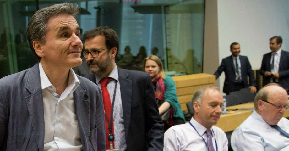 Greek Finance Minister Euclid Tsakalotos (left) waits for the start of the meeting with his eurozone peers. Photo: Michel Euler /Associated Press / AP