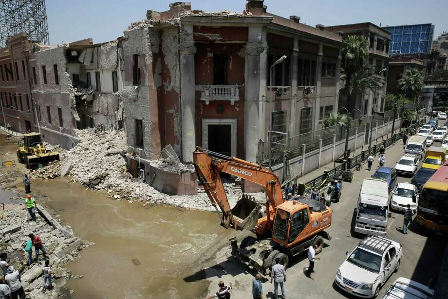 Workers clear rubble at the site of an explosion near the Italian Consulate in, Cairo, Egypt, on Saturday. Italy's foreign minister vowed that his country would not be intimidated the deadly explosion.  (AP Photo/Thomas Hartwell) Photo: Thomas Hartwell, STF / AP