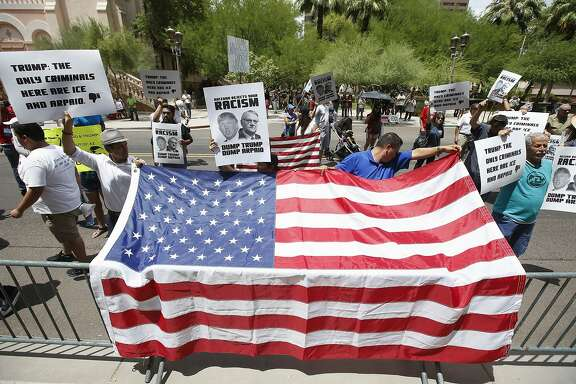 Immigration rights supporters protest in front of the venue where Republican presidential candidate Donald Trump was to speak before a crowd of 3,500 Saturday, July 11, 2015, in Phoenix. (AP Photo/Ross D. Franklin)