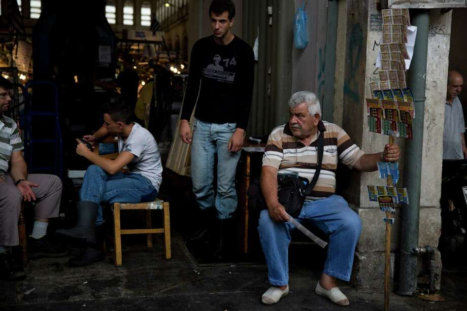People sit in the main gate of a fish market in central Athens on Saturday, while in Brussels, the country's negotiators aim to persuade European finance ministers to grant Greece its third bailout. Without it, the nation would likely be forced to leave the euro. Photo: Petros Giannakouris, STF / AP