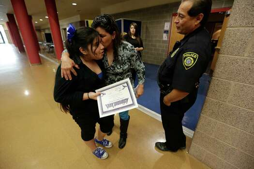 Jessica Guevara (left) gets a kiss on the cheek from her mother, Angie, while chatting with Northeast Independent School District officer Juan Dominguez. Photo: Kin Man Hui / San Antonio Express-News / ©2015 San Antonio Express-News