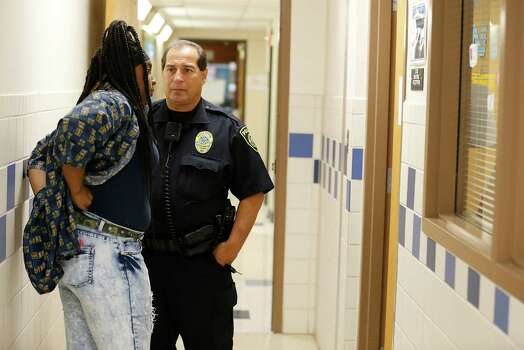 Northeast Independent School District officer Juan Dominguez talks with a students who was involved in a hallway fight with another student at Ed White Middle School on Wednesday, May 20, 2015. The middle school has been part of a three-year pilot program utilizing restorative discipline techniques to stem issues such as physical altercations between students and to promote communication between educators and students in order to lower discipline issues and thus raise academic standards. The approach seems to have had worked but flare-ups like the incident where Dominquez interceded still arise on occasion. The school still intends to utilize the restorative discipline approach. (Kin Man Hui/San Antonio Express-News) Photo: Kin Man Hui, Staff / San Antonio Express-News / ©2015 San Antonio Express-News