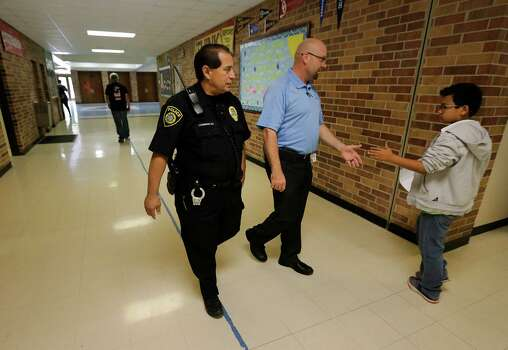 Northeast Independent School District officer Juan Dominguez (left) and Assistant Principal Kevin Curtis walk the halls of Ed White Middle School after a fight between two female students on Wednesday, May 20, 2015. The middle school has been part of a three-year pilot program utilizing restorative discipline techniques to stem issues such as physical altercations between students and to promote communication between educators and students in order to raise academic standards. (Kin Man Hui/San Antonio Express-News) Photo: Kin Man Hui, Staff / San Antonio Express-News / ©2015 San Antonio Express-News