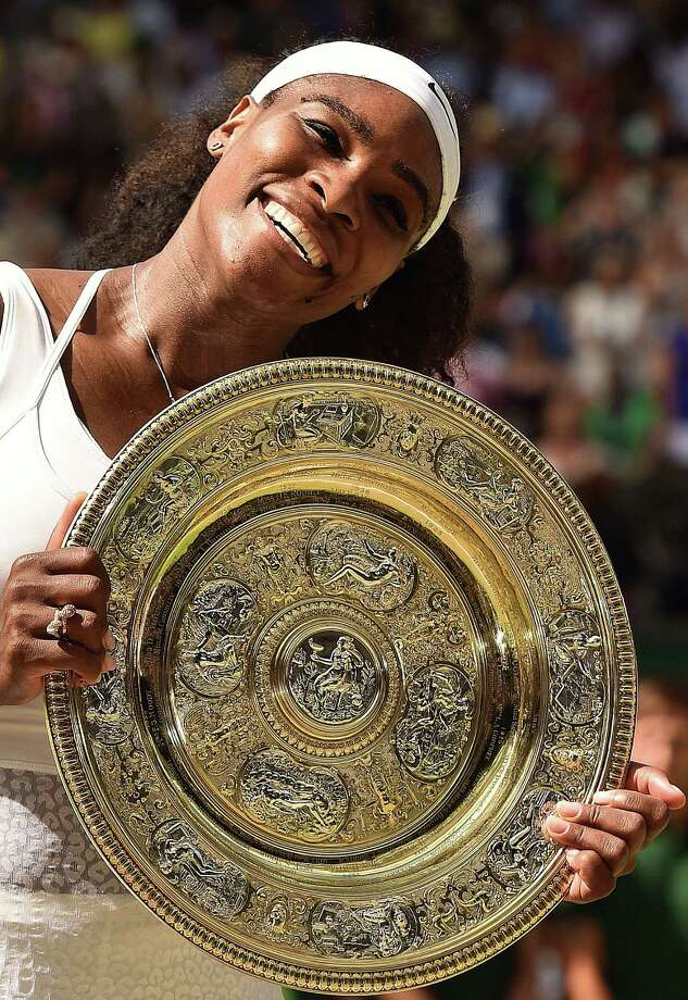 Serena Williams has had a lot of practice posing with the winner's trophy, doing so six times in Wimbledon singles. Photo: LEON NEAL, Staff / AFP