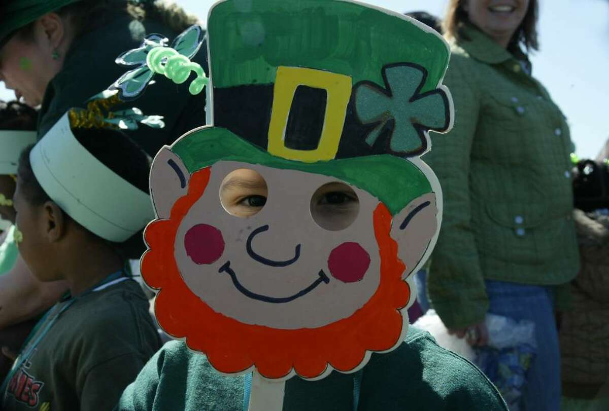 A young leprechaun stares out from behind his mask, Wed., March 18, 2010.