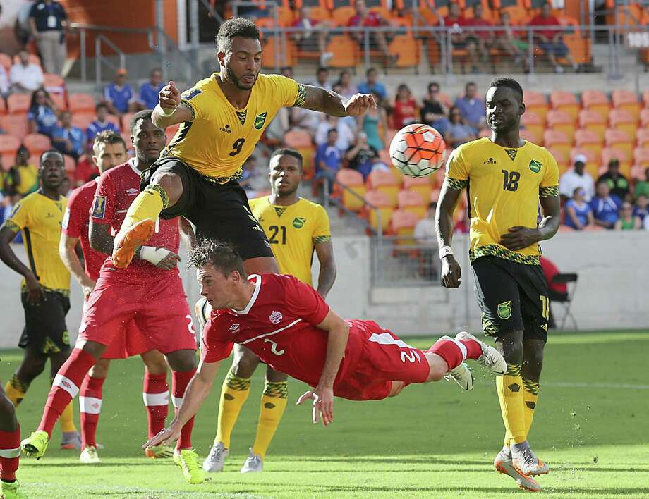 Jamaica's Giles Barnes, left, who traverses the BBVA Compass Stadium field as a forward for the Dynamo, tries to track down a corner kick in the penalty box while avoiding a collision with Canada's Nicolas Ledgerwood on Saturday. Photo: Thomas B. Shea, Freelance / © 2015 Thomas B. Shea
