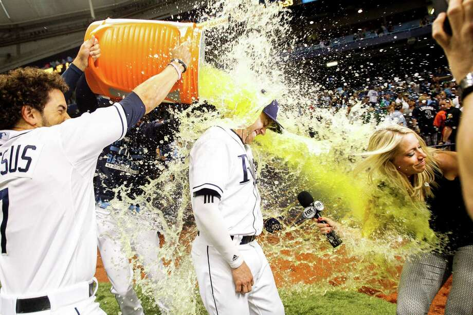 First baseman Jake Elmore, center, is doused in celebration after the Rays topped the Astros 3-0 on Saturday at Tropicana Field. Elmore's walk in the second set up Tampa Bay's three-run inning. Photo: Will Vragovic, MBR / Tampa Bay Times