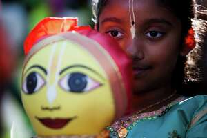 A little girl holds an offering that later made inside of the chariots among other gifts during the Third-Annual Festival of Chariots (India Festival) at Discovery Green, Saturday, July 11, 2015, in Houston.