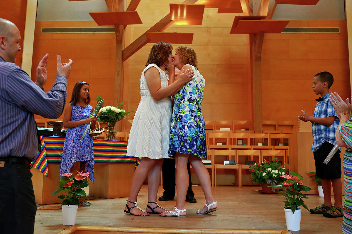 Chris Laguna, left, kisses her wife, Marianne Laguna, as their children, Brynne, 8, and Sam, 11, stand with them as they are pronounced married at First Unitarian Universalist Church of San Antonio on Friday, July 3, 2015. The couple, from Austin, has been together for 18 years and first exchanged vows 15 years ago in a private ceremony.
