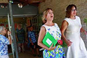 Church members blow bubbles as Marianne Laguna, left, and her wife, Chris Laguna, walk to their reception after their marriage ceremony at First Unitarian Universalist Church of San Antonio on Friday, July 3, 2015.