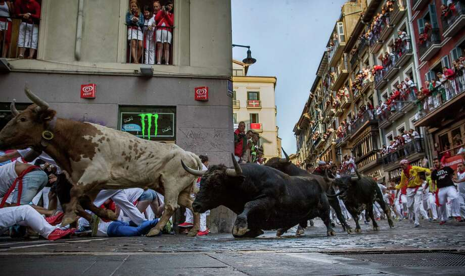 Conde de la Maza fighting bulls run after revelers during the running of the bulls at the San Fermin festival in Pamplona, Spain, Sunday, July 12, 2015. Revelers from around the world arrive to Pamplona every year to take part in some of the eight days of the running of the bulls. Photo: Andres Kudacki, AP / AP