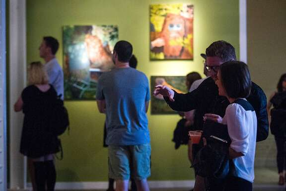 Visitors chat and check out the Ass Kicking Contest exhibit on Saturday, July 11, 2015, at Heron Arts, in San Francisco, Calif.