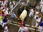 A participant touches the horn of a steer, center, while he runs alongside Estafeta street with Conde de la Maza fighting bulls during the sixth running of the bulls, at the San Fermin Festival, in Pamplona, Spain, Sunday, July 12, 2015. Revelers from around the world arrive to Pamplona every year to take part in some of the eight days of the running of the bulls.