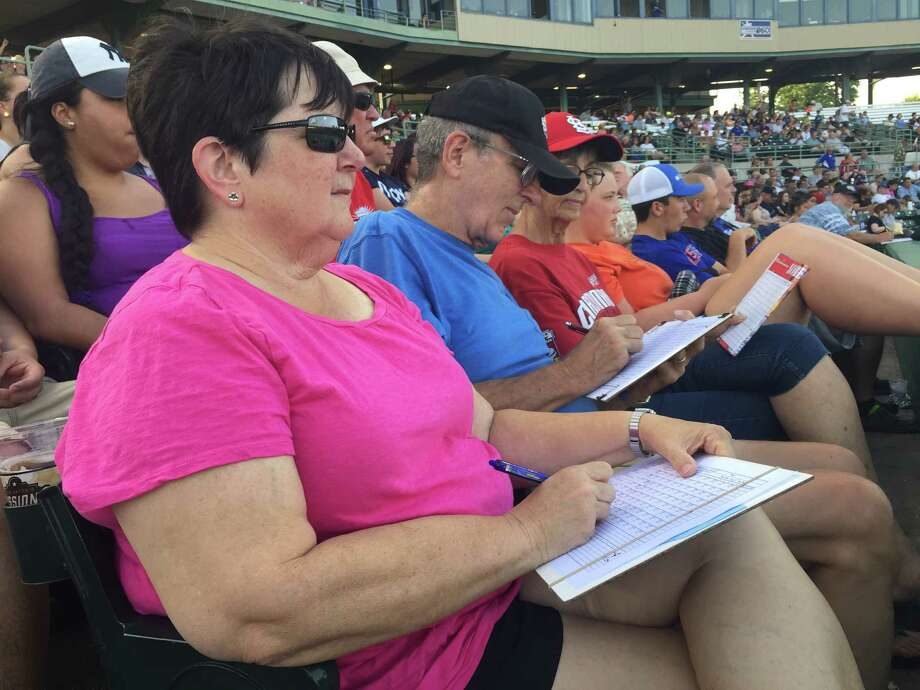 Deb and Dick Lockwood, of Kerrville, sit behind the Missions' dugout at Nelson Wolff field for a game against Springfield last week. The Lockwoods note each play of the game in his and hers scorebooks. They like scoring because it makes them feel as if they're part of the game, and because it helps them understand the nuance of the sport. Photo: Roy Bragg /San Antonio Express-News