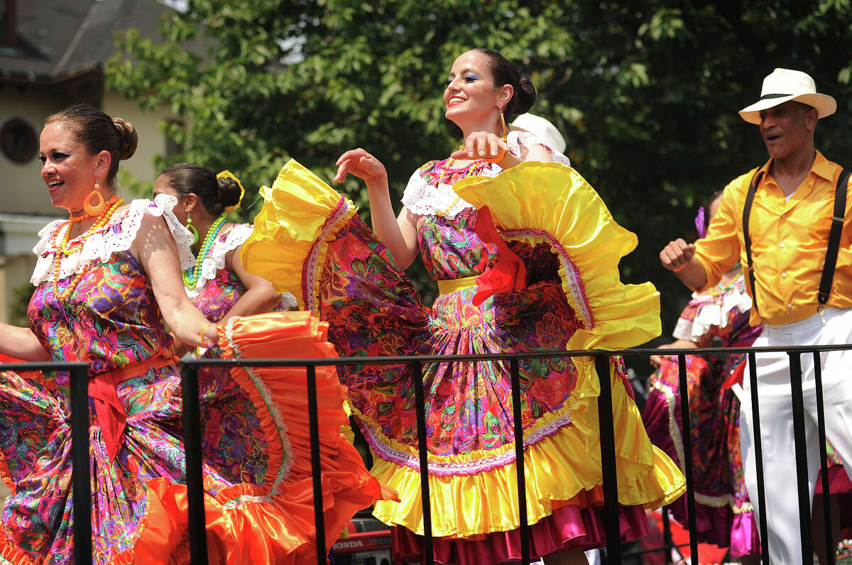 Dancers in traditional costumes dance to salsa music on one of many floats during the Puerto Rican Day Parade on Park Avenue in Bridgeport, Conn. on Sunday, July 12, 2015.