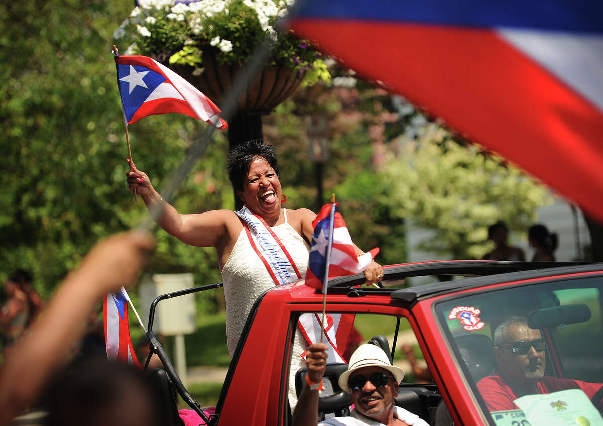 Parade Godmother Janet Ortiz gets into it as she waves the Puerto Rican flag during the annual Puerto Rican Day Parade on Park Avenue in Bridgeport, Conn. on Sunday, July 12, 2015.