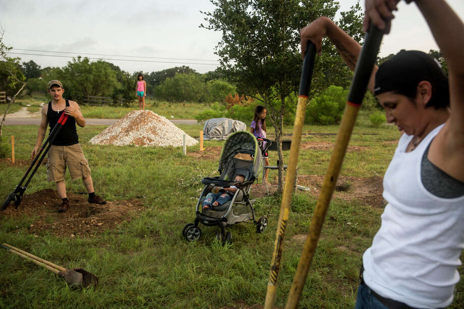 Glenda Bamberger, right, and her husband Jarrell Bamberger, left, widen holes dug in their yard in Blanco, Texas on July 11, 2015.  Their home was destroyed in the floods that occurred in May along the Blanco River in Central Texas.  They poured a concrete pillar in each of the twelve holes for the house they are building to replace the one that flooded.  The house will be eight feet off the ground in the hope that it will not be affected by future floods on their property. Photo: Carolyn Van Houten, Staff / San Antonio Express-News / 2015 San Antonio Express-News