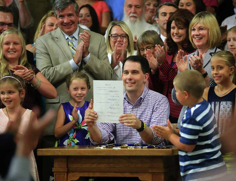 Wisconsin Gov. Scott Walker displays a signed 2015-2017 state budget Sunday during a ceremony on the production floor of Valveworks USA in Waukesha. Photo: John Hart, MBO / Wisconsin State Journal