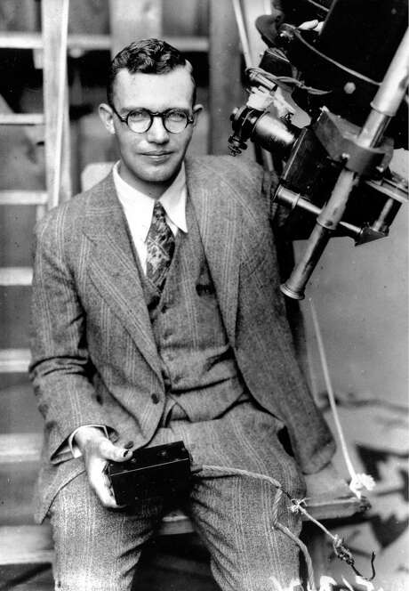 In this 1931 photo, Clyde Tombaugh poses with the telescope through which he discovered the Pluto. NASA's New Horizons spacecraft carries a canister containing his ashes. Photo: STR / ap