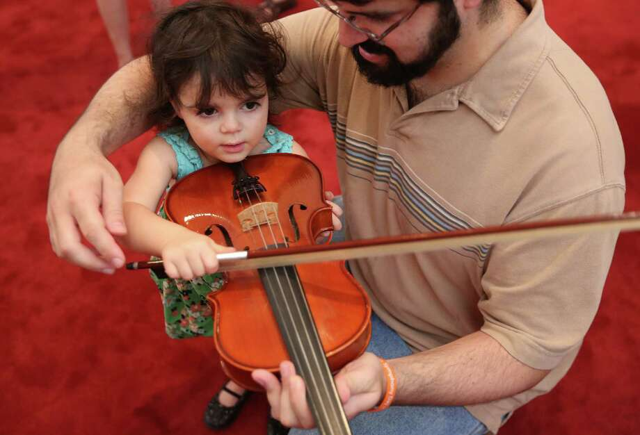 Razel Hofrichter holds a violin with the help of her father  Michael Hofrichter while visiting the instrument petting zoo during the 3rd Annual Houston Symphony Free Day of Music at Jones Hall on Sunday, July 12, 2015, in Houston. Visitors rotate between several different stages to hear jazz groups, Tejano, blues bands, and other groups representing Houston's diverse community. Photo: Mayra Beltran, Houston Chronicle / © 2015 Houston Chronicle