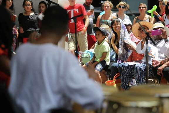 The crowd listens to Joy of Djembe Drumming perform on the Outside Patio Stage during the 3rd Annual Houston Symphony Free Day of Music at Jones Hall on Sunday, July 12, 2015, in Houston. Visitors rotate between several different stages to listen to jazz groups, Tejano, blues bands, and other groups representing Houston's diverse community.