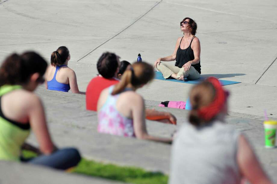 Yoga Instructor Diane Simpson leads a group of people in a session outside at Riverfront Park on Sunday morning, July 12, 2015, in Troy, N.Y.  This is the second year of the yoga in the park program, which is put on by Heartspace Yoga and Healing Arts and the Troy BID.  The free Sunday morning yoga event runs through August 16th.     (Paul Buckowski / Times Union) Photo: PAUL BUCKOWSKI / 00032423A