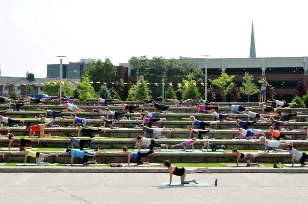 Yoga Instructor Diane Simpson, foreground, leads a group of people in a session outside at Riverfront Park on Sunday morning, July 12, 2015, in Troy, N.Y.  This is the second year of the yoga in the park program, which is put on by Heartspace Yoga and Healing Arts and the Troy BID.  The free Sunday morning yoga event runs through August 16th.     (Paul Buckowski / Times Union) Photo: PAUL BUCKOWSKI / 00032423A