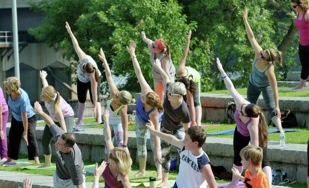 Women, men and children take part in a yoga session outside at Riverfront Park on Sunday morning, July 12, 2015, in Troy, N.Y.  This is the second year of the yoga in the park program, which is put on by Heartspace Yoga and Healing Arts and the Troy BID.  The free Sunday morning yoga event runs through August 16th.   (Paul Buckowski / Times Union) Photo: PAUL BUCKOWSKI / 00032423A
