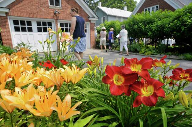 Daylilies are seen blooming as people make their way to the backyard garden at 8 Pinewood Ave. on Sunday, July 12, 2015, in Saratoga Springs, N.Y.  This backyard garden was one of the locations for the Saratoga Secret Gardens Tour.  The Secret Gardens Tour is sponsored by Soroptimist International of Saratoga County as a fundraiser for the organization.  The Soroptimist International of Saratoga County is an organization made up of business and professional women who work to improve the lives of women and girls in the community.   (Paul Buckowski / Times Union) Photo: PAUL BUCKOWSKI / 00032580A
