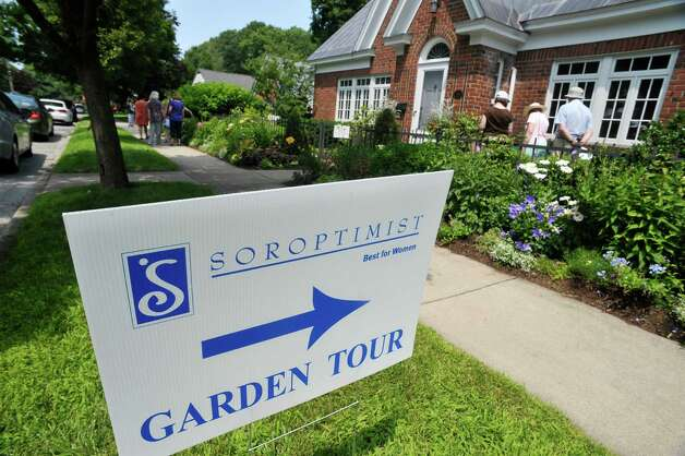 People make their way in to see  the garden at 8 Pinewood Ave. on Sunday, July 12, 2015, in Saratoga Springs, N.Y.  This backyard garden was one of the locations for the Saratoga Secret Gardens Tour.  The Secret Gardens Tour is sponsored by Soroptimist International of Saratoga County as a fundraiser for the organization.  The Soroptimist International of Saratoga County is an organization made up of business and professional women who work to improve the lives of women and girls in the community.   (Paul Buckowski / Times Union) Photo: PAUL BUCKOWSKI / 00032580A