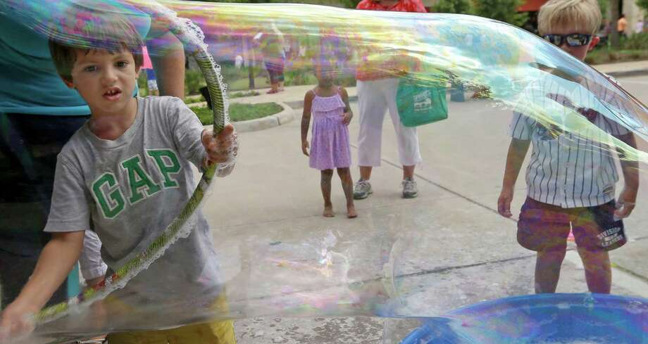 Alex Vargas, 5, makes a soap bubble with a hula hoop during the Creekside Park Village Green grand opening on Saturday. Photo: Melissa Phillip, Staff / © 2015  Houston Chronicle