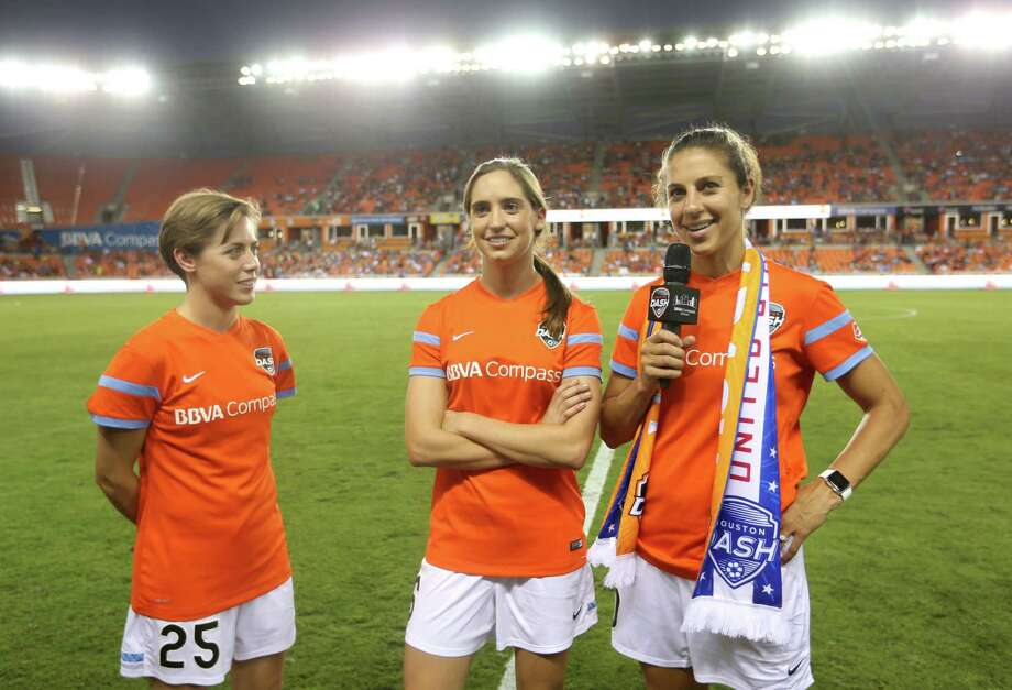 Houston Dash defender Meghan Klingenberg (25), Houston Dash midfielder Morgan Brian (6) and Houston Dash midfielder Carli Lloyd (10), members of the world champion United States Women's soccer team, greet the fans during halftime of the Houston Dash vs. Chicago Red Stars game at BBVA Compass Stadium Sunday, July 12, 2015, in Houston. Photo: Jon Shapley, Houston Chronicle / © 2015 Houston Chronicle