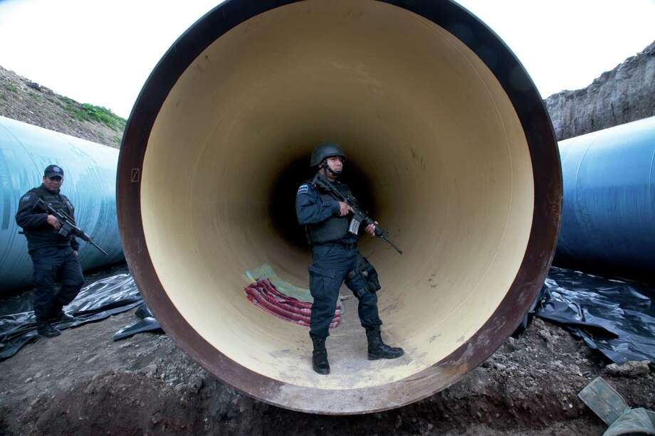 Federal police guard a drainage pipe outside of the Altiplano prison Sunday after Joaquin Guzman fled through a hole in the shower that led to a tunnel. Photo: Marco Ugarte, STR / AP