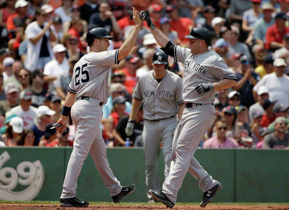 New York Yankees' Brian McCann, right, is welcomed home by teammate Mark Teixeira, left, after hitting a two-run home run off a pitch by Boston Red Sox starting pitcher Wade Miley in the second inning of a baseball game at Fenway Park, Sunday, July 12, 2015, in Boston. Teixeira also scored on the hit. (AP Photo/Steven Senne) ORG XMIT: MASR105 Photo: Steven Senne / AP