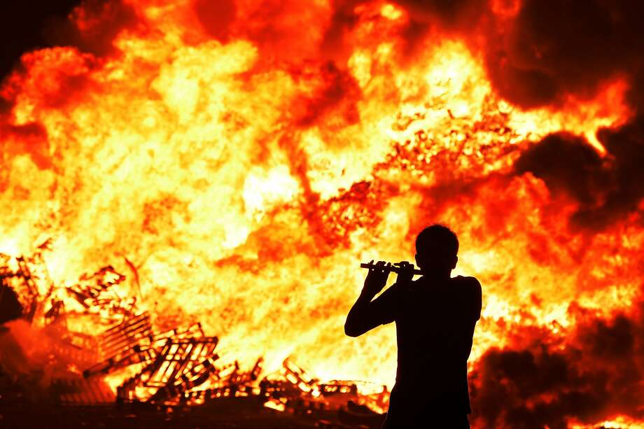 Iain McFarland, an Orange bandsman, plays his flute during the 11th night bonfire at the New Mossley housing estate on July 12, 2015 in Belfast, Northern Ireland. New Mossley is widely recognised as the largest bonfire in the province. Tradition holds that the bonfires commemorate the lighting of fires on the hills to help Williamite ships navigate through Belfast Lough at night when Protestant King William III and his forces landed at Carrickfergus to fight the Catholic Jacobites, supporters of the exiled Catholic King James II. The bonfires also mark the beginning of the annual 12th of July Orange parades. Photo: Charles McQuillan