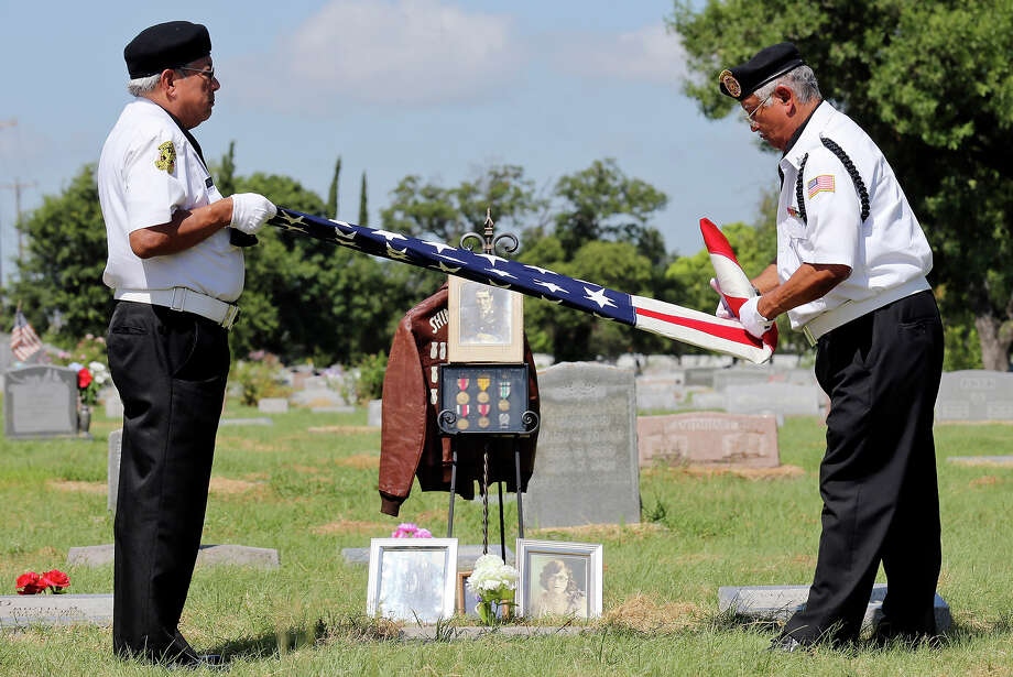 VFW Post 76 Honor Guard members Cris Vieyra Jr., left, and Santiago Tello fold an American flag on Sunday during a memorial ceremony in San Antonio at the grave of Sgt. Leroy Moore, who died 65 years ago during the Korean War. Photo: Edward A. Ornelas, Staff / © 2015 San Antonio Express-News